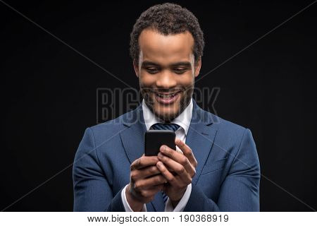 Portrait Of Businessman In Formalwear Typing On Smartphone Isolated On Black