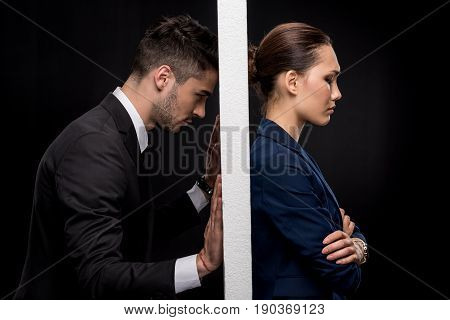 Side View Of Sad Couple In Formal Wear Separated By Wall Isolated On Black