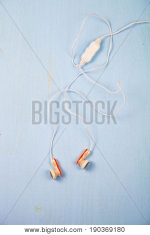 White little headphones on blue wooden table close-up