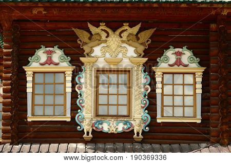 Russian carved wooden frames beautify exterior of timbered house.