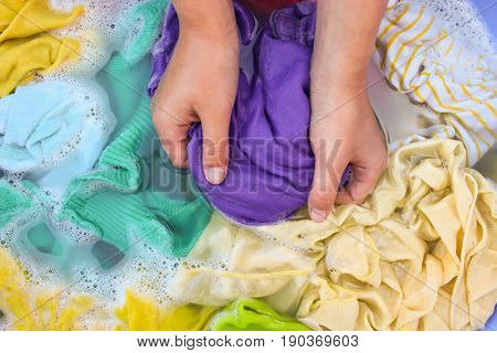 Female hands wash colored clothes in basin. poster