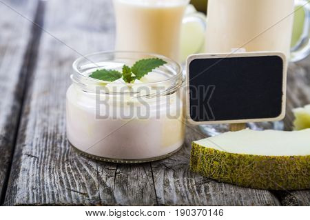 Yogurt And Smoothie With Melon On A Wooden Table.