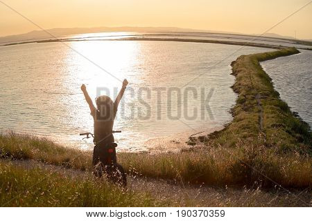 Silhouette of happy boy with open arms riding his bike at sunset, enjoying the nature, beautiful trail winding ahead through the bay.