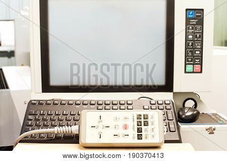 Operation pult keypad and display on the control panel of industrial machine in workshop. Indoors close-up.