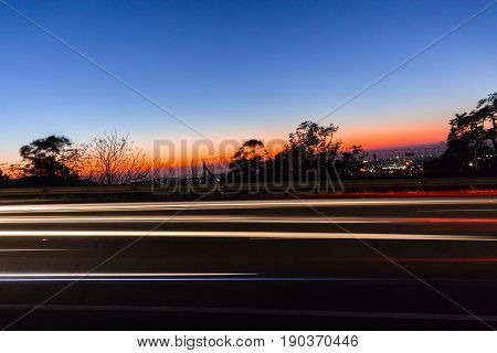 Vehicles cars lights speed blurs dawn travelling traffic motion colors.