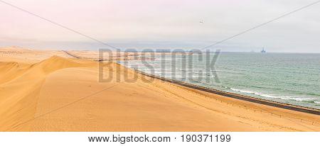 Long Road Across Dunes Of Kalahari Desert With Atlantic Seaside, Near To Swakopmund Town, Namibia