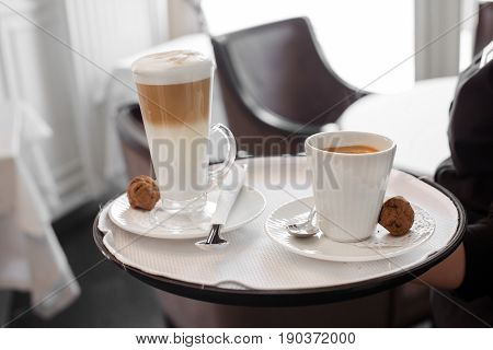 Anonymous server holding tray with served cups of coffee.
