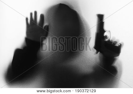 Shadow Blur Of Horror Man In Jacket With Hood Gun In His Left Hand And Right Hand Touches The Glass.