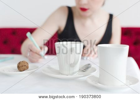 Anonymous woman sitting at table with cups and writing.