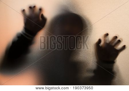 Shadow Blur Of Horror Man In Jacket With Hood.hands On The Glass.dangerous Man Behind The Frosted Gl