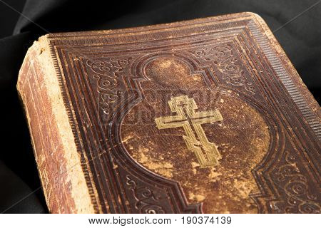 Old Book On Black Background. Ancient Christian Bible. Close Up Antique Holy Scripture Book. Cross O