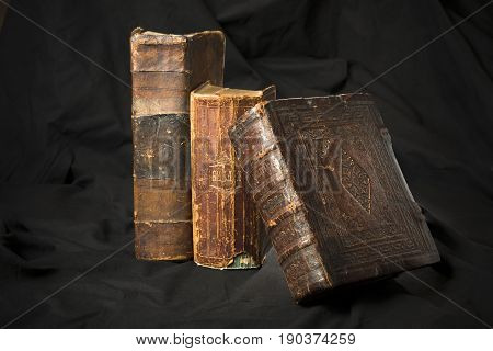 Old Book Spines On Black Background. Ancient Library. Antique Holy Scripture Books. Antique Books Co