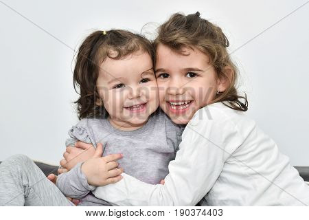 Hugging and smiling sisters cheek to cheek