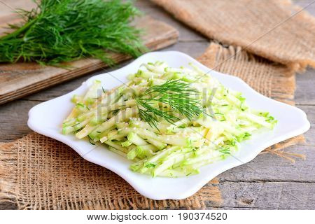 Zucchini ribbon salad with cheese. Healthy salad with fresh zucchini, cheese and chopped dill on a plate. Simple and quick summer salad. Rustic style. Closeup