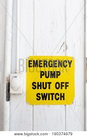 Emergency pump shut off or stop push button switch sign on wood board