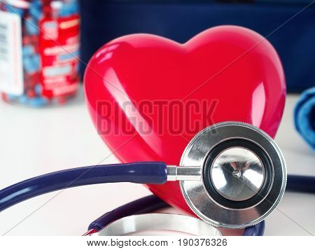Red toy heart and stethoscope laying on cardiologist working table. Healthcare medical cardiology and prevention of cardiovascular diseases concept.