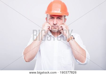Portrait Of Contractor Wearing Hardhat Covering His Ears