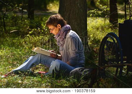 Disabled woman reading a book in the forest wheelchair