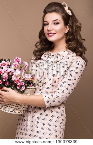 Fresh young girl in a light silk dress, smile, retro curls in the style of pin-up with a basket of flowers in her hands. Beauty face and body. Photos shot in studio