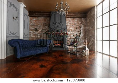 Interior with fireplace, candles, skin of cows, brick wall, large window and of a loft, living room, coffee table and dark blue sofa in modern design