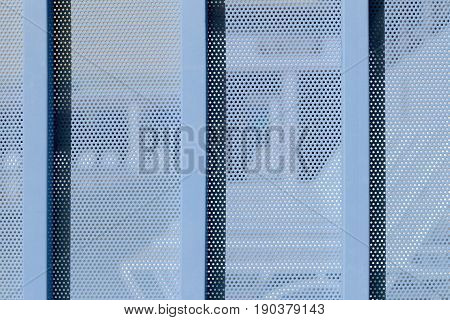 blue Background sheet of metal covered with lines of circular holes