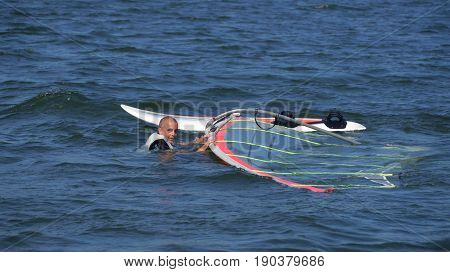 Windsurfing, man in the water at the board, on the lake Niesłysz Polish