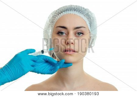 close-up portrait of a girl in a medical cap at the doctor who makes the prick on her face isolated on white background