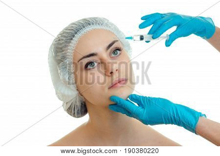 Portrait of a young girl in the medical cap at beautician gloves which makes incisions on the face isolated on white