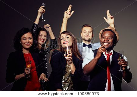 Group portrait of cheerful young people posing for photography with champagne flutes in hands while clubbing, dark background