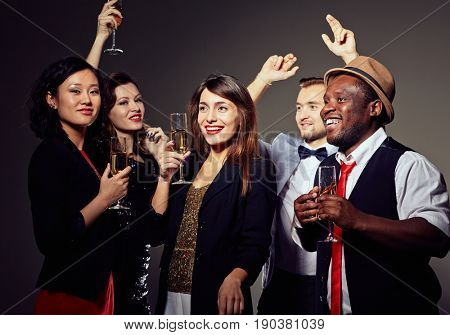 Waist-up portrait of pretty young woman looking away with charming smile and holding champagne flute in hand, her friends standing next to her and enjoying New Year party