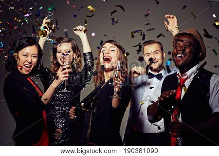 Waist-up portrait of beautiful young woman with champagne flute in hand grinning from ear to ear while celebrating momentous event with best friends