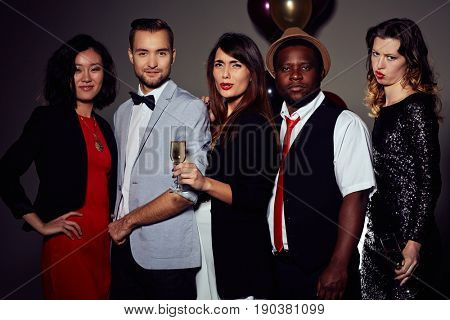 Group portrait of young friends wearing stylish clothes celebrating Christmas in night club, attractive young woman with dissatisfied facial expression holding champagne flute in hand