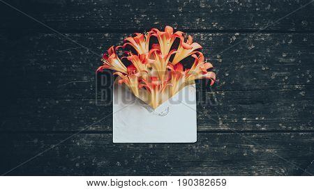 yellow spring flowers in envelope on wood background. Concept: flower delivery.