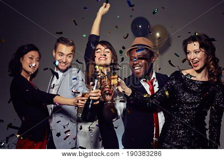 Having New Year party in nightclub: multi-ethnic group of friends dancing and posing for photography with champagne flutes in hands, colorful confetti falling on background