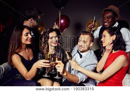 Multi-ethnic group of young people gathered together at home party in order to celebrate birthday of their friend, they toasting with champagne and wishing very best