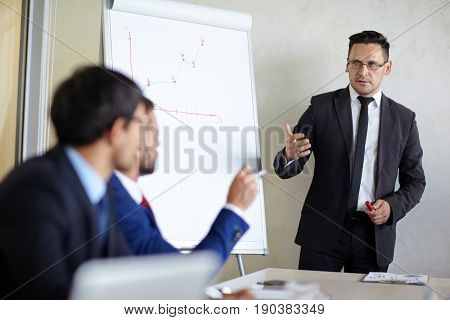 Middle-aged entrepreneur standing at marker board and discussing possible methods of improving company financial condition with coworkers