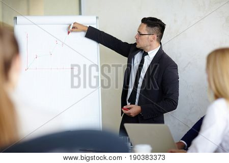 Waist-up portrait of bearded businessman standing at dry-erase board and drawing chart, his colleagues listening to him with concentration
