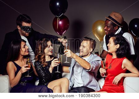 Multi-ethnic group of friends gathered together at home party and having fun, they holding champagne flutes in hands