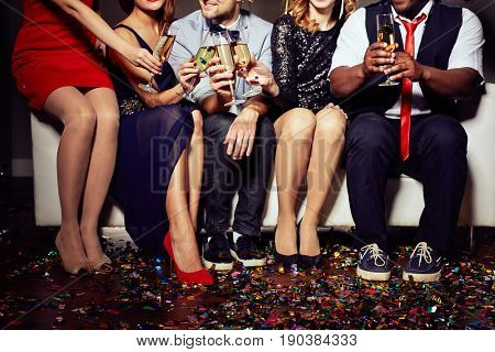 Close-up shot of unrecognizable young friends sitting on sofa and clinking champagne flutes together, floor covered with colorful confetti