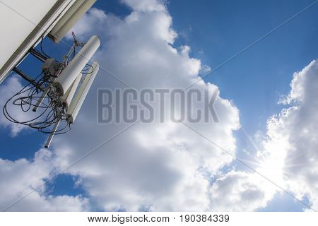 radio, tv or telephone transmitter with blue sky clouds and sunlight.