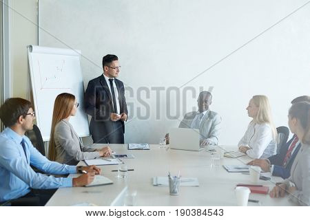 Group of white collar workers gathered together in modern board room while having training session