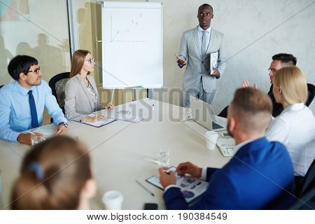 Group of young white collar workers analyzing financial report data while having work meeting in modern board room