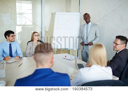 Multi-ethnic team of talented managers discussing growth strategy of their company while sitting in modern board room