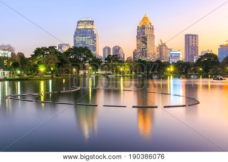 Reflection business district building from a park with night scene from Lumpini Park Bangkok Thailand