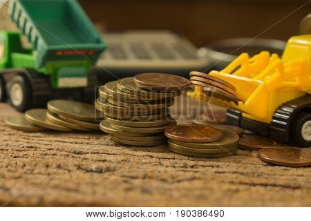 money saving and growth concept idea image of struck with truck toy and stack of coins
