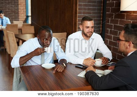 Three businessmen in formalwear gathered together in cozy cafe and discussing their joint project during coffee break