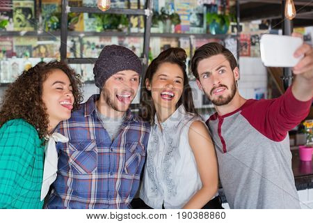 Group of friends making faces while talking selfie in restaurant