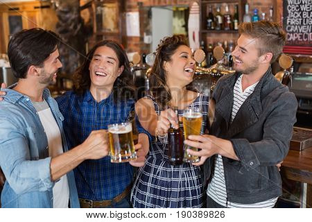 Cheerful friends tossing beer glasses and bottles in pub