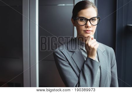 Counselor in glasses with hand on chin at office