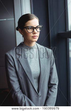 Counselor in glasses at office looking away